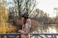 Young woman walking near lake in park adorable knitted hat and having fun autumn Royalty Free Stock Photo