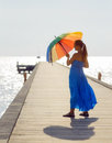 Young woman walking on the pier with umbrella Stock Photos