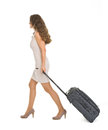 Young woman walking with wheels suitcase Royalty Free Stock Image