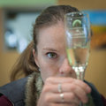 The young woman wanders over a glass of sparkling wine
