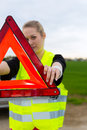 Young woman with warning triangle on street Stock Image