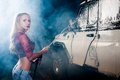 Young woman washing car pretty offroad by foam hose Royalty Free Stock Photography