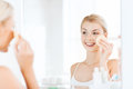 Young woman washing face with sponge at bathroom Royalty Free Stock Photo