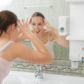 Young woman washing her face with clean water in bathroom Royalty Free Stock Image