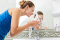 Young woman washing her face with clean water in bathroom Stock Images