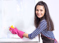 Young woman washing window housewive smiling happy cleaning Royalty Free Stock Photography