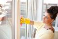 Young woman washing windows in the flat Stock Photo