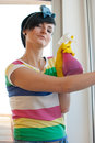 Young woman washing windows in the flat Stock Images