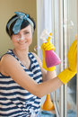 Young woman washing windows in the flat Stock Image