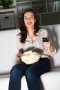 Young woman watching tv on the couch eating popcorn Royalty Free Stock Photo