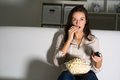 Young woman watching tv on the couch eating popcorn Royalty Free Stock Image