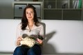 Young woman watching tv on the couch eating popcorn Royalty Free Stock Images