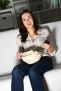 Young woman watching tv on the couch eating popcorn Stock Photo