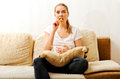 Young woman watching TV and eating chips Royalty Free Stock Photo