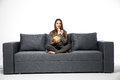 Young woman watching TV and eating chips sitting on sofa Royalty Free Stock Photo