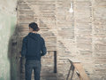 Young woman by wattle and daub wall a is standing a Stock Photos