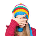 Young woman wearing colorful hat hiding behind her hand cute caucasian knitted and scarf isolated on white background Royalty Free Stock Images