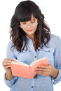 Young woman wearing glasses and reading her book on white background Stock Image