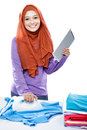Young woman wearing hijab reading article on tablet while ironin Royalty Free Stock Photo