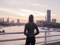 Young woman wearing hoodie on bridge in London at sunrise Royalty Free Stock Photo