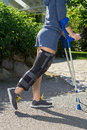 Young woman wearing a leg brace side view an adjustable to support and immobilize her knee post operative walking outdoors on Stock Photos