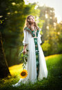 Young woman wearing a long white dress holding a sunflower outdoor shot. Portrait of beautiful blonde girl with sunflower Royalty Free Stock Photo