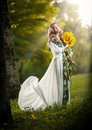 Young woman wearing a long white dress holding sunflowers outdoor shot. Portrait of beautiful blonde girl with yellow flowers Royalty Free Stock Photo