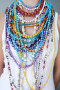 Young woman wearing multi coloured beads and necklaces close up of many strings of different of different colours shapes sizes Royalty Free Stock Photos