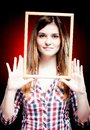 Young woman wearing plaid shirt holding wooden frame around her face Royalty Free Stock Image