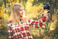 Young woman wearing plaid shirt with retro photo camera taking selfie shot outdoor hipster lifestyle sunny forest nature on Royalty Free Stock Photos