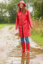 Young woman wearing raincoat playing in a puddle Royalty Free Stock Photo