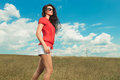 Young woman wearing sunglasses walking in the fields Royalty Free Stock Photo