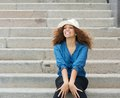 Young woman wearing white hat and sitting on stairs portrait of a Stock Photos