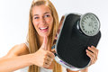 Young woman with weight scale diet and a she is happy about her success Royalty Free Stock Images
