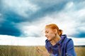 Young woman in wheat field wearing blue sweater on a cloudy day Royalty Free Stock Photos