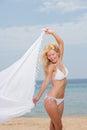 Young woman in white bikini holding sarong on the beach windy Stock Image