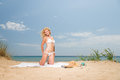 Young woman in white bikini holding sarong on the beach windy Stock Photos