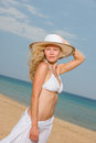 Young woman in white bikini holding sarong on the beach windy Stock Photography