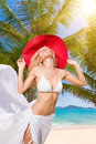 Young woman in white bikini holding sarong on the beach windy Stock Photos