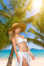 Young woman in white bikini holding sarong on the beach windy Royalty Free Stock Photos