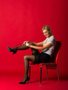 Young woman in a white blouse and black skirt corrects stocking sitting on chair Stock Images