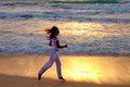 The young woman in white clothes in runs in the area of a surf silhouette running on sunset along ocean coast Royalty Free Stock Images
