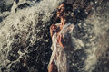 Young woman in white shirt and bikini stands in water flows near Royalty Free Stock Photo