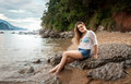 Young woman in white shirt relaxing on rock at sea shore beautiful Royalty Free Stock Images