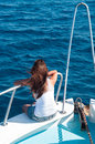 Young woman in white singlet on shipboard brunette caucasian female bow of yacht with legs out back view Royalty Free Stock Image