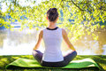 Young woman in white top practicing yoga in beautiful nature. Meditation in morning sunny day Royalty Free Stock Photo