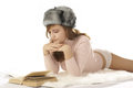 A young woman in a winter hat reading a book Royalty Free Stock Photography