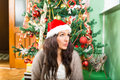Young woman wondering about christmas presents and new year gift gifts girl wearing santa hat thinking holiday decoration Royalty Free Stock Photography