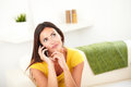 Young woman wondering while talking on cell phone Royalty Free Stock Photo