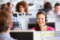 Young woman working in call centre, surrounded by colleagues Royalty Free Stock Photo